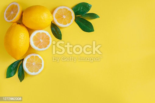 Composition of lemons, slices, green leaves are laid out in triangle on upper left corner of yellow background. Citrus fruit for preparing cocktails, beverages, drinks. Vitamin C concept.