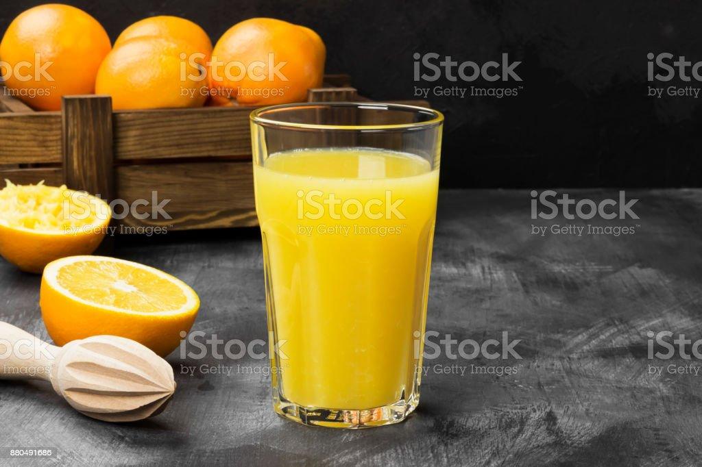 Oranges and fresh orange juice on a black background