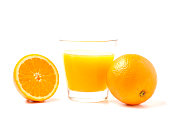 Two fresh ripe oranges next to a freshly squeezed glass of orange juice.