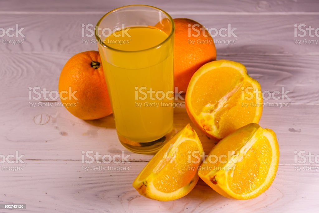 Oranges and glasses with orange juice on a wooden table - Foto stock royalty-free di Agricoltura