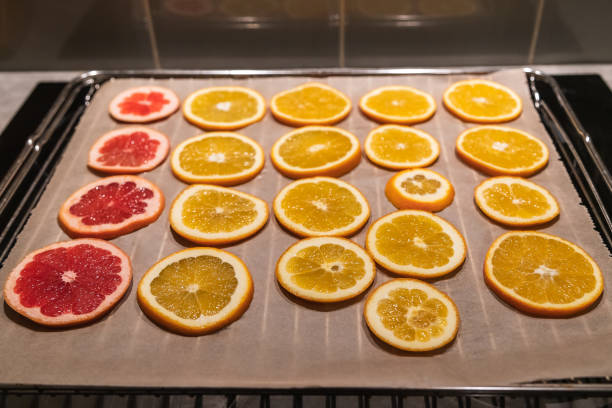 oranges and graprfruit on a tray to be dried for diy projects and zero waste Christmas decorations stock photo