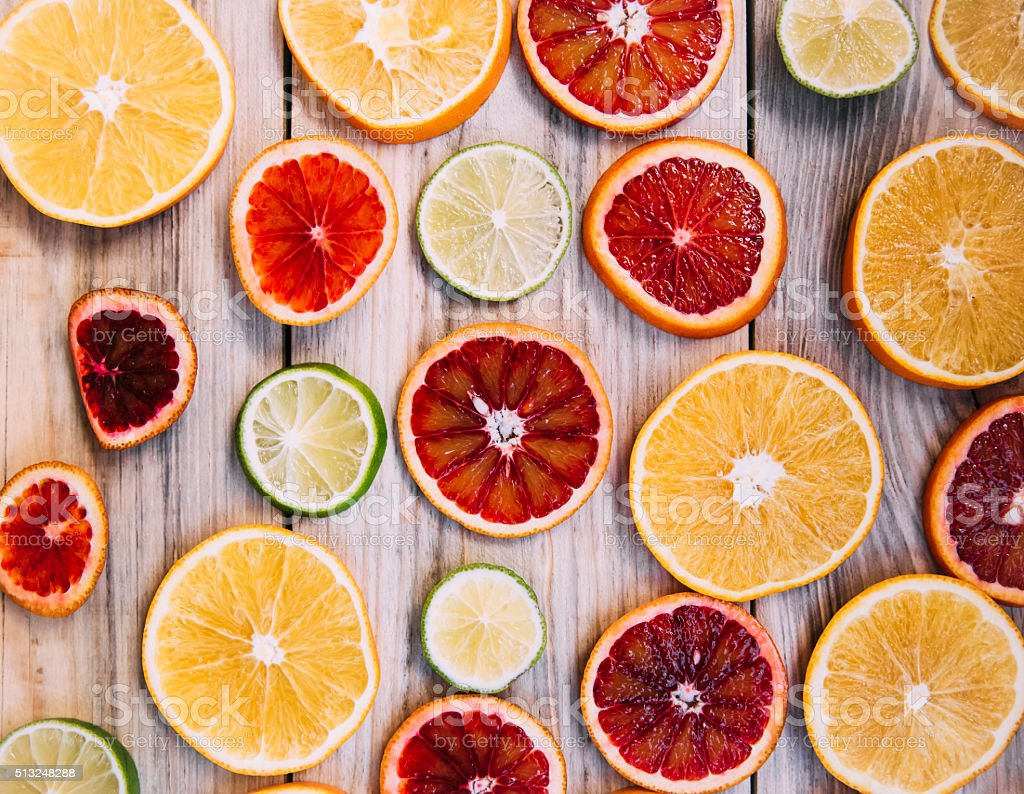 Oranges and lime slices on the wooden table stock photo