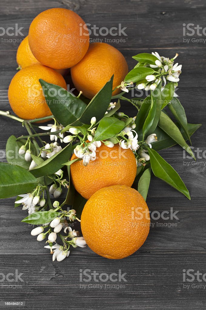 Oranges and orange blossom on dark wooden table stock photo