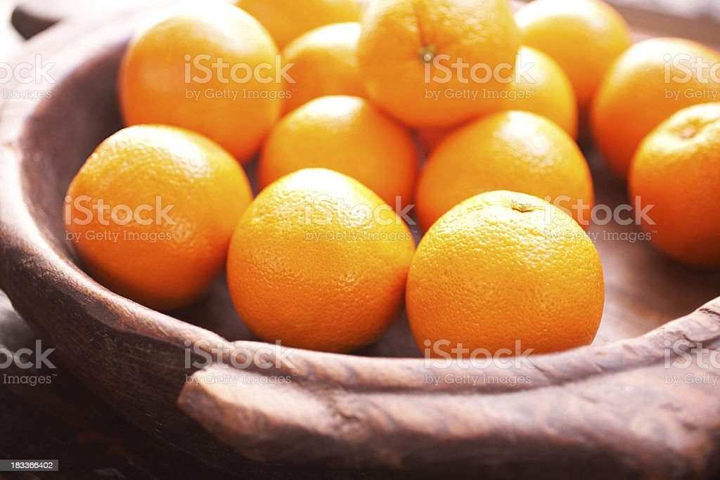 Oranges in wooden bowl on table royalty-free stock photo