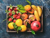 istock Oranges, lemons, pomegranate, bananas, strawberries and persimmon in wooden box 867023984
