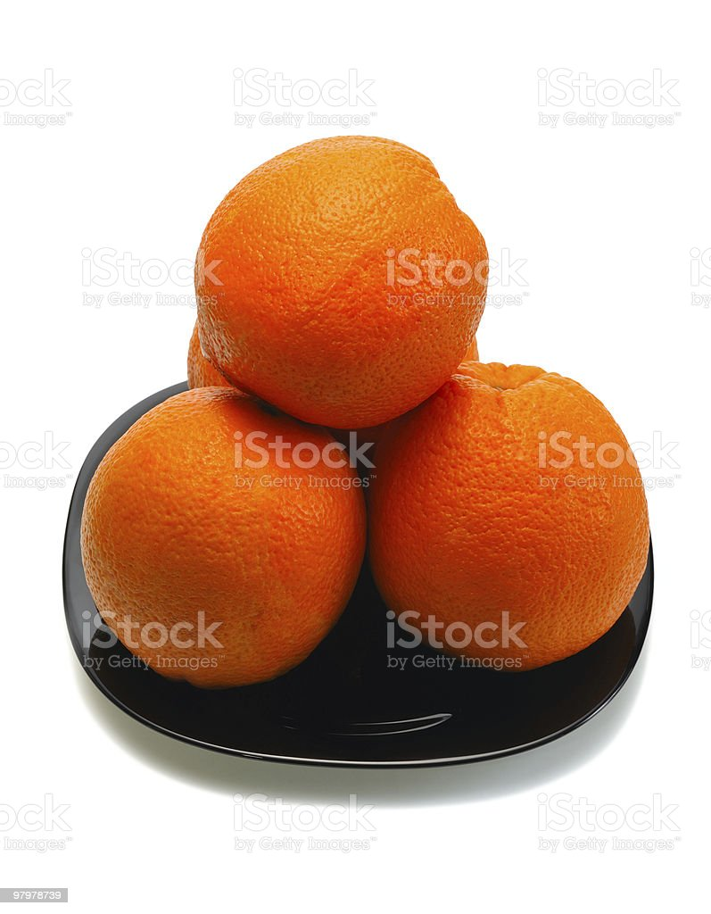 Oranges on a black plate, white background royalty-free stock photo