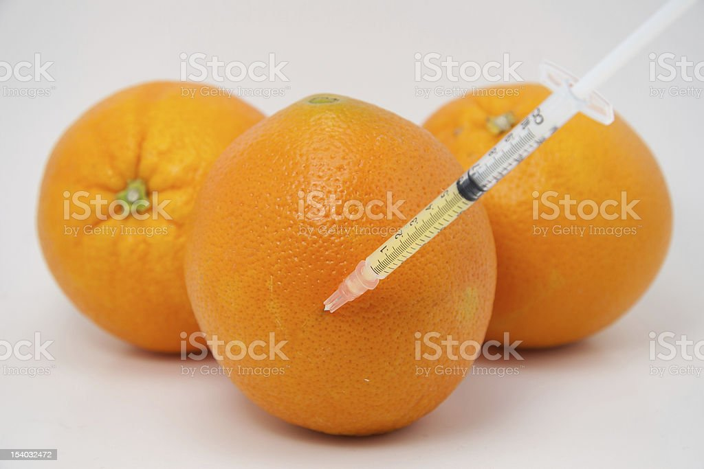 Oranges with a syringe of juice royalty-free stock photo