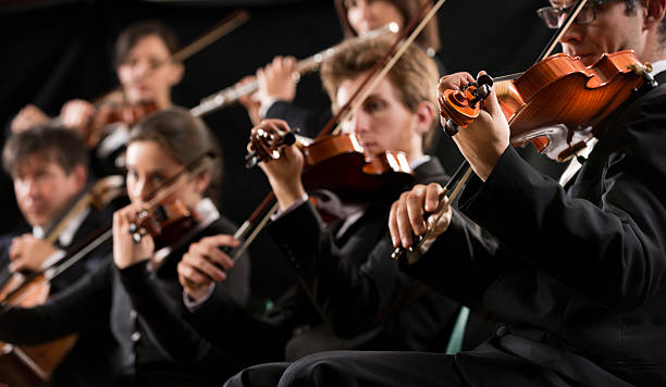 Orchestra first violin section Symphony orchestra first violin section performing on dark background. string instrument stock pictures, royalty-free photos & images
