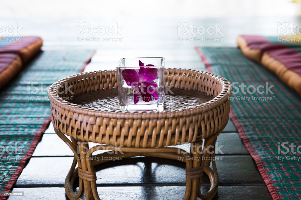 orchid flower in glass. Thai backrest pillow on mat. Thailand scatter cushion mattress for spa massage. comfortable & relax concept stock photo