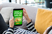 istock Order food online concpet.Woman lying down on sofa using tablet see restaurant menu online at home.digital technology lifestyle. 1138137907