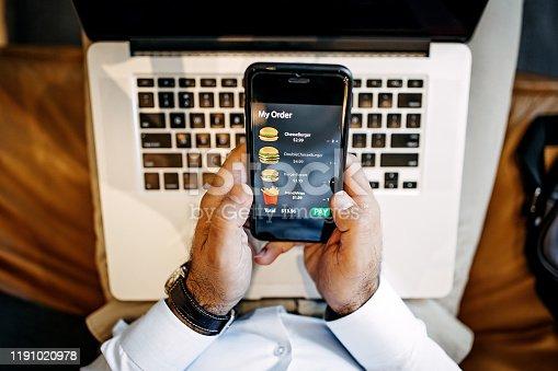Man ordering food online using mobile phone app