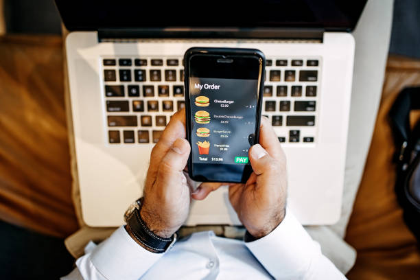 Order food online Man ordering food online using mobile phone app ordering stock pictures, royalty-free photos & images