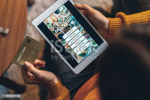 Unrecognizable person with digital tablet and credit card ordering food online