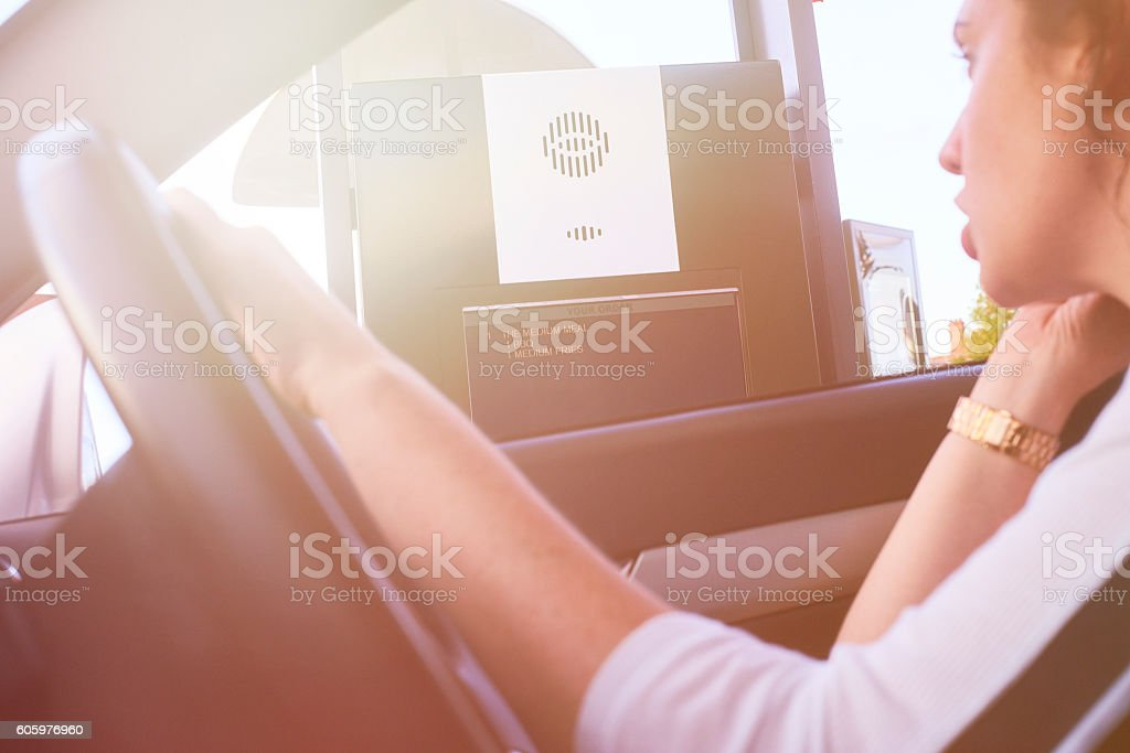Ordering fast food at the drive through stock photo