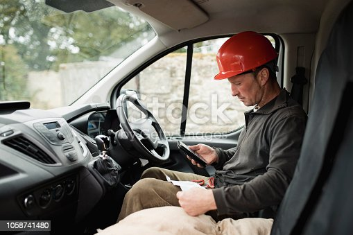 Mid-adult male joiner sitting in a van with his weimaraner dog next to him. he is using his phone and has some notes for materials with him.