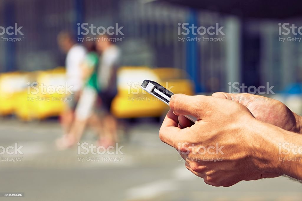 Ordering taxi Hands of man ordering taxi, using mobile phone app 2015 Stock Photo