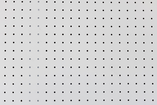 orderly dot or holes rows and columns on white pegboard wall.