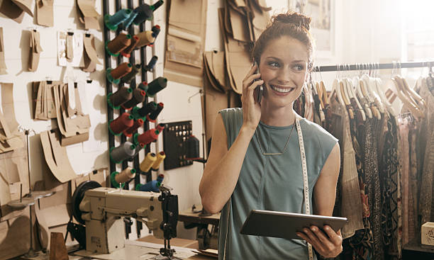 Orders come in and she gets them right out! Shot of a young dressmaker in her workshop doing business over the phone and onlinehttp://195.154.178.81/DATA/istock_collage/a5/shoots/785349.jpg craftsperson stock pictures, royalty-free photos & images