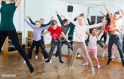 Ordinary boys and girls studying contemp dance in dancing studio