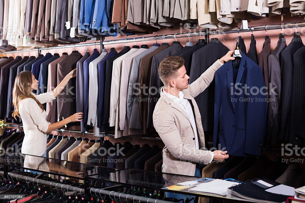 Ordinary couple examining various suits stock photo