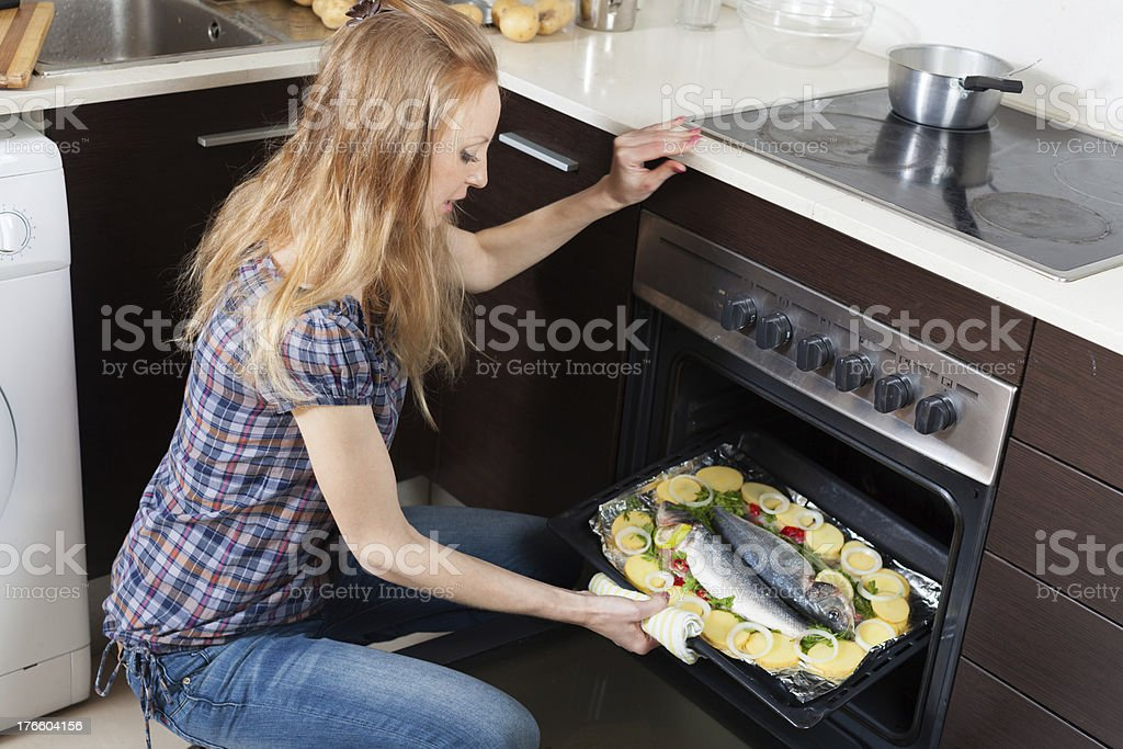 Ordinary girl cooking raw fish in oven royalty-free stock photo