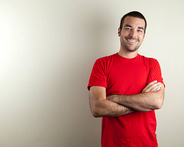 "Ordinary man smiling ""An ordinary man with red t-shirt on beige background, smiling. Copy space."" red shirt stock pictures, royalty-free photos & images"