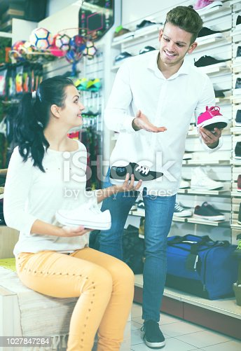 istock Ordinary seller demonstrating sneakers to female 1027847264