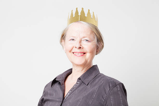 ordinary senior woman wearing a crown stock photo
