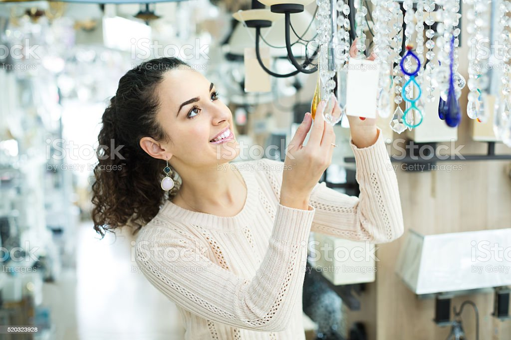 Ordinary woman doing shopping in lighting shop stock photo