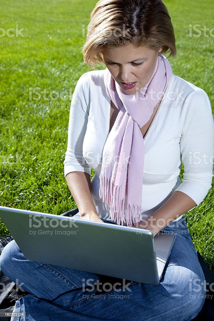 ordinary woman sitting cross-legged on grass, using laptop royalty-free stock photo