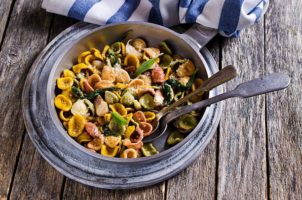 Orecchiette Pasta with garlic and sage Orecchiette pasta of different colors with garlic and sage. Selective focus. orecchiette stock pictures, royalty-free photos & images