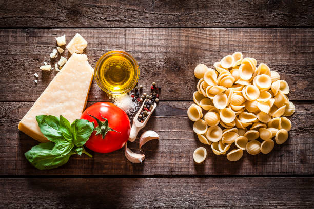 Orecchiette pasta with ingredients on rustic wooden table Top view of orecchiette pasta with ingredients for cooking pasta composition shot on rustic wooden table. The composition includes Parmesan cheese, tomato, basil, garlic cloves, peppercorns, salt and olive oil. Predominant color is brown. Low key DSRL studio photo taken with Canon EOS 5D Mk II and Canon EF 100mm f/2.8L Macro IS USM orecchiette stock pictures, royalty-free photos & images