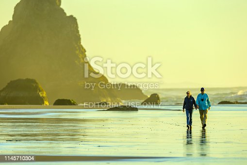 Oregon coast USA on February 09, 2016: Couple walking on Bandon Beach on the Oregon Coast