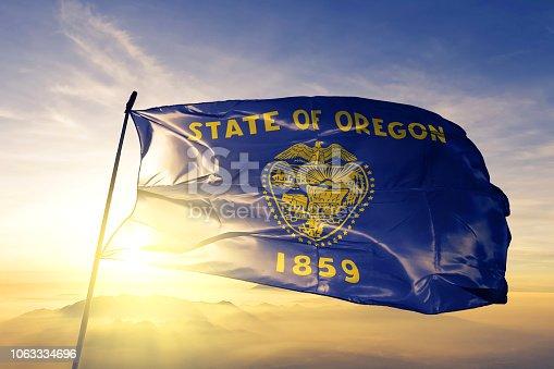 Oregon state of United States flag on flagpole textile cloth fabric waving on the top sunrise mist fog
