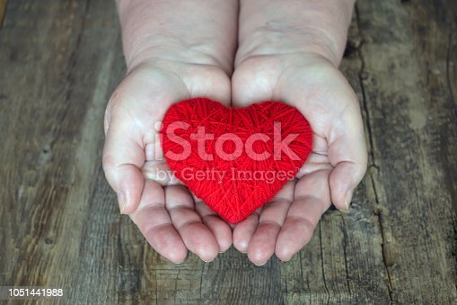 istock Organ donation, help someone. Adult woman hands giving thread red heart. Hands of adult woman, mother holding a red heart in the palm on dark wooden background 1051441988