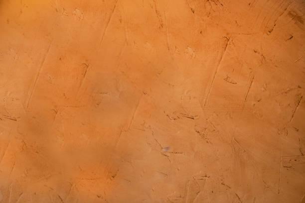 organgish rugueux stuc boue grunge fond où vous pouvez voir les marques où il a été appliqué - adobe photos et images de collection