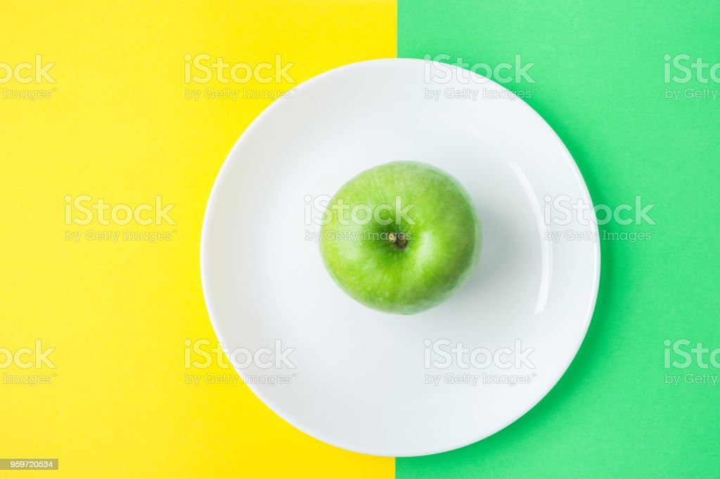 Organic Apple on White Plate on Duotone Yellow Green Background. Vitamins Healthy Diet Spring Summer Detox Vegan. Poster Banner Template. Mock up with Copy Space stock photo