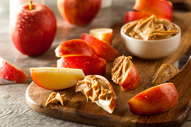 organic apples and peanut butter - pindakaas stockfoto's en -beelden