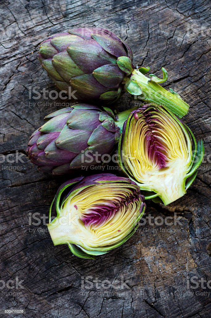 Organic Artichokes on  rustic wooden board stock photo