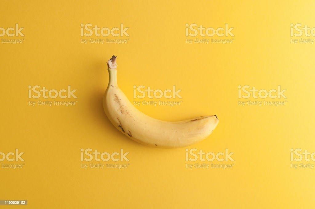 Organic banana on bright yellow background - Стоковые фото Банан роялти-фри