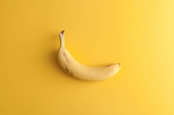 organic banana on bright yellow background - k logo стоковые фото и изображения