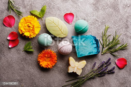 Bath spa accessories on rustic background, colorful bath bombs and soap bars with flowers and herbs.