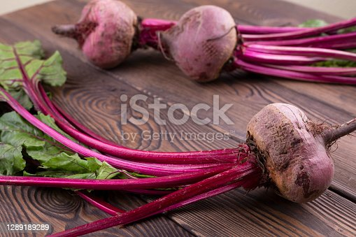 istock Organic Beetroot,red beetroot with herbage green leaves on rustic background. 1289189289