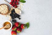 Oatmeal, honey, Raspberries, Strawberries and blueberries in flat lay design.