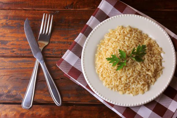 organic brown rice grain cooked in white dish on rustic wooden table. integral rice top view - dieta macrobiotica foto e immagini stock