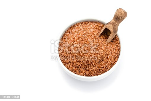 Top view of a little bowl filled with brown sugar crystals isolated on white background. A wooden measuring spoon is in the bowl. High key DSRL studio photo taken with Canon EOS 5D Mk II and Canon EF 100mm f/2.8L Macro IS USM