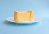 Close up of organic butter on white plate against blue background (selective focus)
