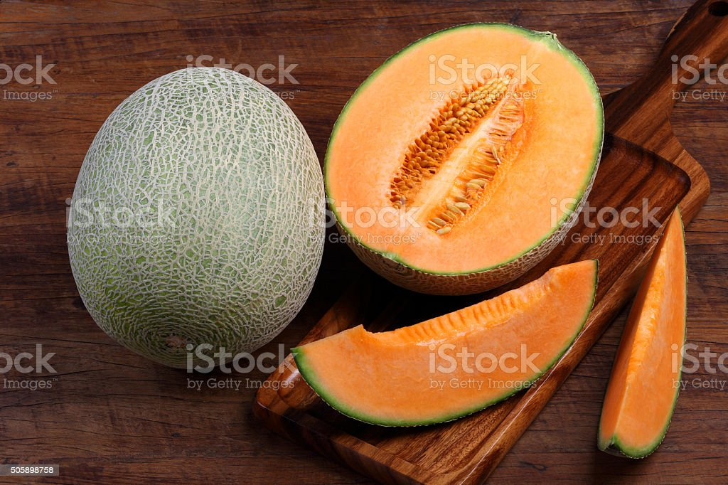 Organic cantaloupe with utensils on wooden table stock photo