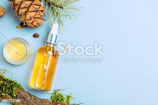 istock Organic cedar oil and cedar cone on a blue background. Flat lay. Beauty blogger concept. 994713298