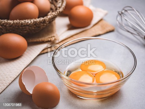 Close up image of three eggs yolk in clear bowl are one of the food ingredients on the restaurant table in the kitchen to prepare for cooking. Organic chicken eggs food ingredients concept